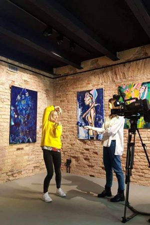 Painter Monisha giving interview for TV in her exhibition
