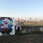 Artist Monisha standing near secret painting in Vilnius lithuania