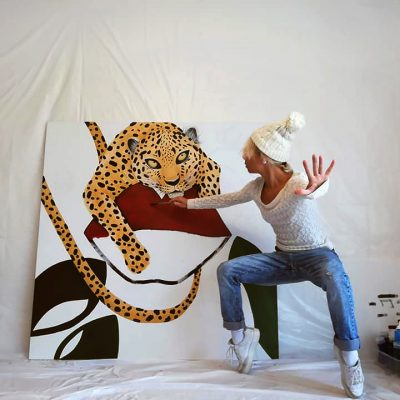 Artist Monisha painting on canvas in a dance move